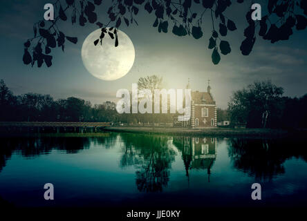 Ghost house at night at the lake in moonlight - Stock Photo