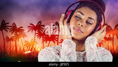 Digital composite of Happy casual woman listenning music with headphones in front of plam trees background - Stock Photo