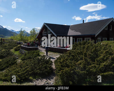 Visitors dining out in the sunshine at a cafe close to Engabreen glacier in Svartisen National Park Norway - Stock Photo