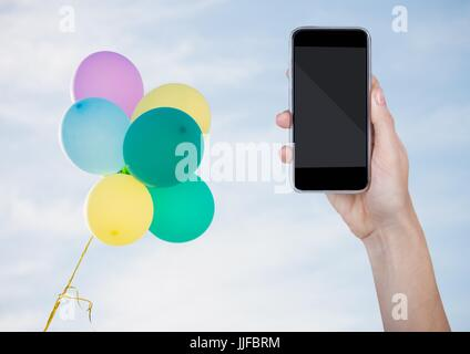 Digital composite of Hand with phone against sunny sky and balloons - Stock Photo
