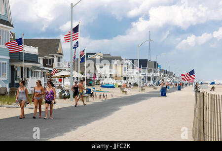 People strolling along Manasquan's beach front walkway in New Jersey. - Stock Photo