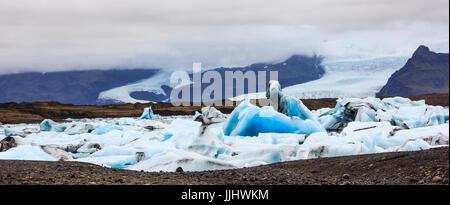 Stunning winter day view of Jokulsarlon, glacial river lagoon, large glacial lake, southeast Iceland, on the edge - Stock Photo