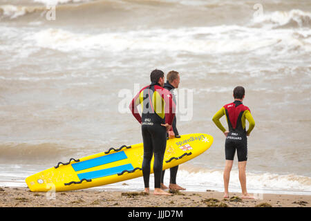 Male lifeguards of the RNLI on the shore looking out to rough seas at the popular coastal resort of Rhyl in Denbighshire, - Stock Photo