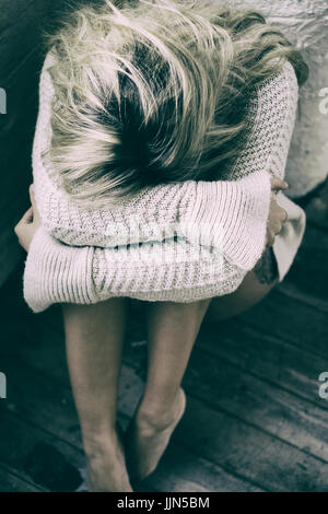 Miserable young woman sitting on the floor crying - Stock Photo