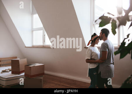 Indoor shot of loving young couple moving into their new home. Man and woman in love standing together with cardboard - Stock Photo