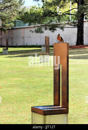 A robin sits atop a memorial chair at the Oklahoma City National Memorial of the bombing of the federal building. - Stock Photo