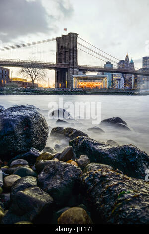 Manhattan Bridge and NYC Skyline at night with reflection of  the skyline on East River - Stock Photo