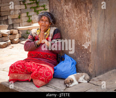 Woman with dog begging on street General street scenes in Kathmandu and Durbar Square,,Nepal,Himalaya, - Stock Photo