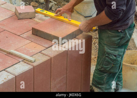 Man cutting stone slabs, concrete slab with an electric grinder - Stock Photo
