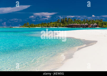 Over water villas in Maldives and a white sandy beach with palm trees - Stock Photo