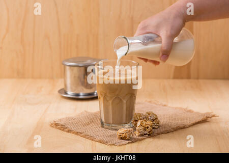 Pouring milk in to glass of coffee on a wooden table. - Stock Photo