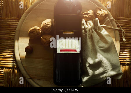 Red wine, walnuts on a wooden background - Stock Photo