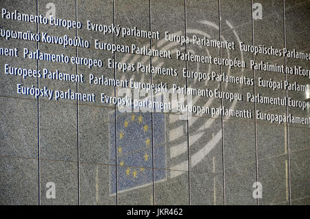 Brussels, Belgium. European Parliament Building. All the languages of the EU and reflection of the Parliament symbol - Stock Photo