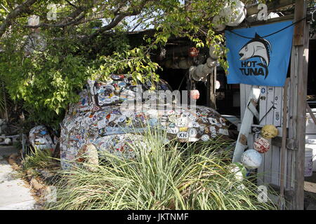 Decorated old vehicle hidden between trees with Hot Tuna flag, Key West Florida - Stock Photo