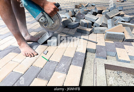 The worker cuts a bar of paving slabs for the final laying on the terrace - Stock Photo