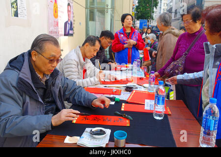 HONG KONG, CHINA - JANUARY 26, 2017: Unidentified people writting wisshes over a red paper contain meaning for Chinese - Stock Photo