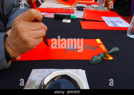HONG KONG, CHINA - JANUARY 26, 2017: Chinese calligraphy on red paper contain meaning for Chinese New Year wishes - Stock Photo
