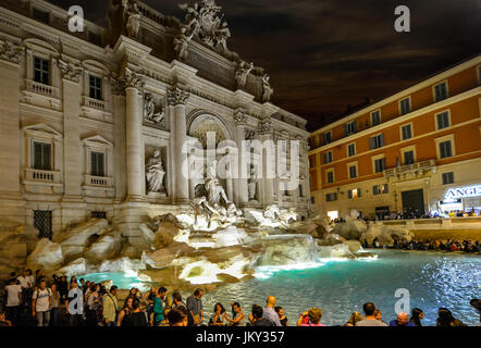 Warm summer night in Rome Italy as crowds of tourists enjoy the Trevi Fountain and the nightlife in a busy piazza - Stock Photo