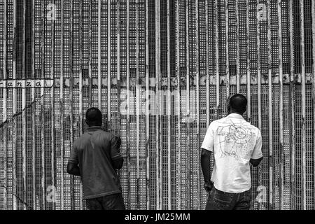 Tijuana, Baja California, Mexico. 25th June, 2017. Haitian migrants communicate with American citizens on the other - Stock Photo