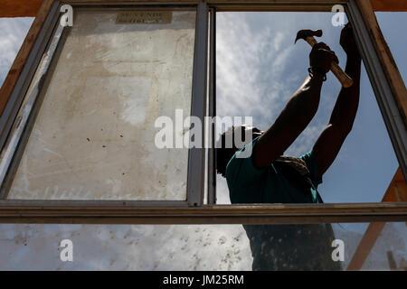 Tijuana, Baja California, Mexico. 19th July, 2017. A Haitian migrant installs a window of a structure along a dry - Stock Photo