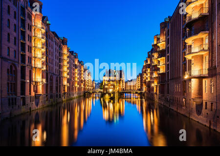 Canal Warehouses in Downtown District of Hamburg Germany at dusk - Stock Photo