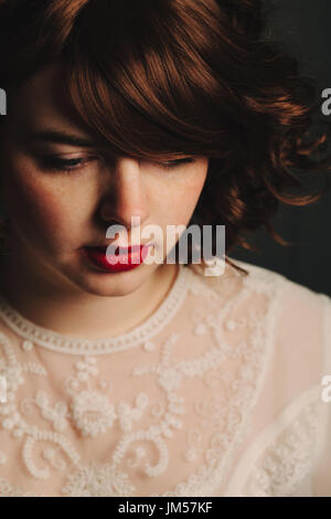 Young woman girl with brunette curly hair and red lips looking down and wearing a vintage white lace top - Stock Photo
