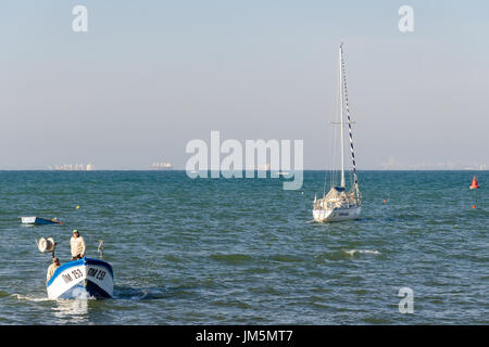 Fishermen in small boat approaching the coast with couple of large ships in background, Pomorie, Bulgaria - Stock Photo