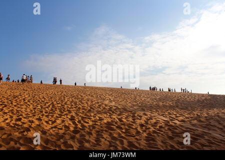 Mui Ne, Vietnam - June 27, 2017: Tourist walking around at red sand dunes in the morning - Stock Photo