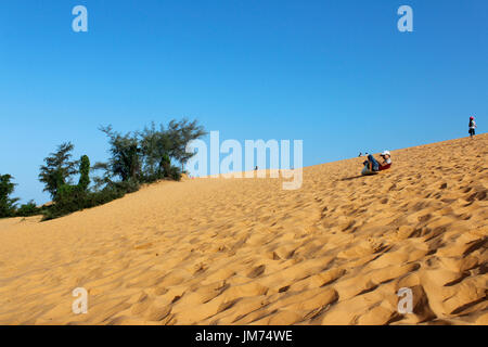 Mui Ne, Vietnam - June 27, 2017: A child sand boarding with the slide board - Stock Photo