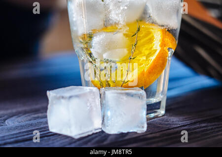 Alcoholic drink with lemon and ice in a glass on a old dark wooden table. Close up view of cold drink - Stock Photo