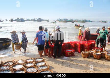 Mui Ne, Vietnam - June 27, 2017: Crowded scene of daily early morning fish market on beach - Stock Photo