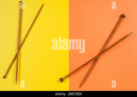 Brown wooden knitting needles on yellow and orange background - Stock Photo