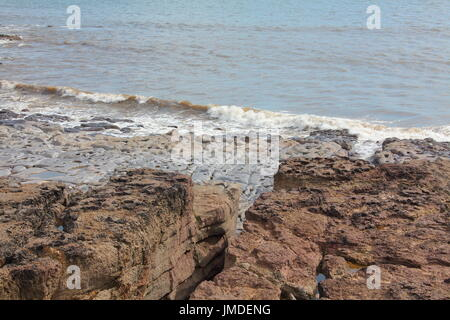 Small waves breaking onto the base of large heavily cracked rock formation lining the coast, lower rocks smoothed - Stock Photo
