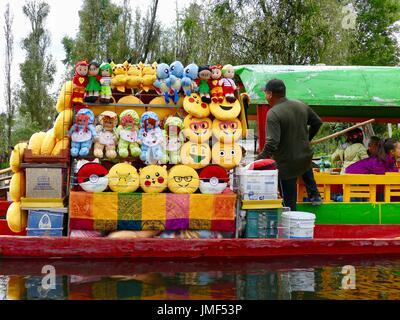 Boat vendor selling tourist items, dolls, pillows, Xochimilco, Mexico City, Mexico. - Stock Photo