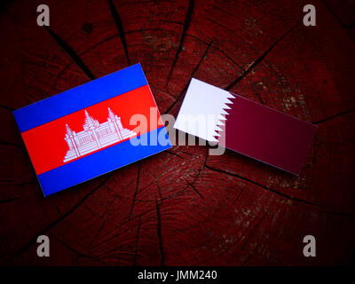 Cambodian flag with Qatari flag on a tree stump isolated - Stock Photo