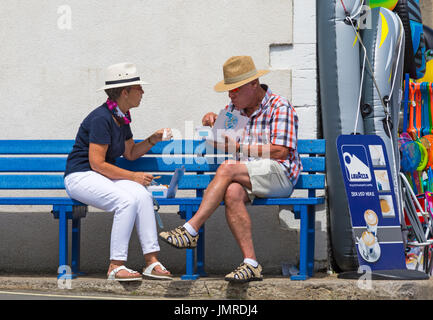Couple sitting on bench eating fish and chips at Lyme Regis, Dorset in July - Stock Photo