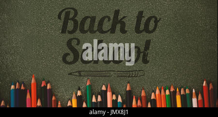 Back to school text over white background against overhead view of colored pencils on gray table - Stock Photo