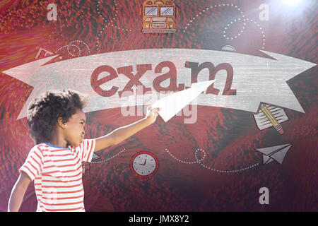 Playful boy playing with paper airplane against exam against black background - Stock Photo