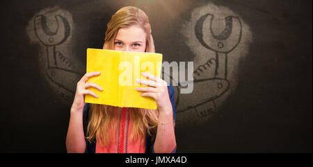 Student covering face with book in library  against blackboard - Stock Photo