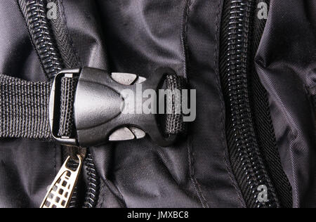 closeup of buckles, clasps, zippers, pockets, fasteners, fittings and seams in the black backpack - Stock Photo