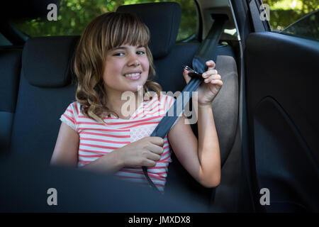 Portrait of happy teenage girl wearing seat belt in the back seat of car - Stock Photo