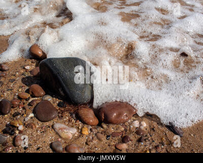 Water laps over smooth, rounded pebbles on a beach. - Stock Photo