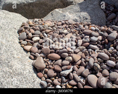 Worn and rounded pebbles forming interesting patterns in the gaps between the rocks of a rock armour groyne on a - Stock Photo