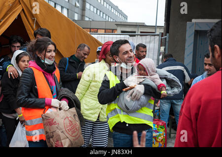 Munich, Germany -September 7th, 2015: A group of Syrian refugees with a small baby are very happy to arrive at the - Stock Photo