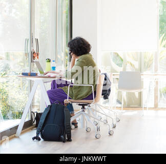 Young female college student studying with laptop in the university library/study room - Stock Photo