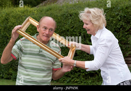 Elderly couple playing with a gold picture frame - Stock Photo
