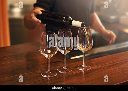 Sommelier pours pinot gris wine in glasses for degustation - Stock Photo