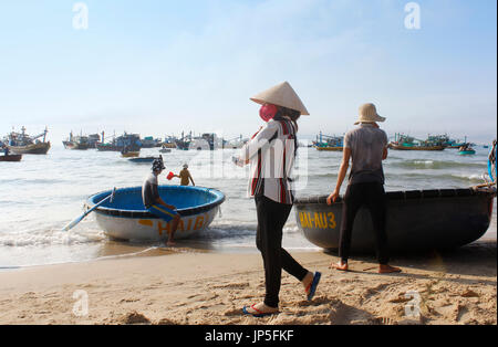 Mui Ne, Vietnam - June 27, 2017: Crowded scene of daily early morning fish market on beach with the Vietnamese woman - Stock Photo