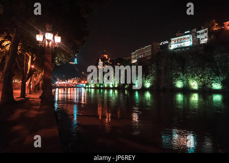 Evening view of Tbilisi and the Kura river at dusk - Stock Photo
