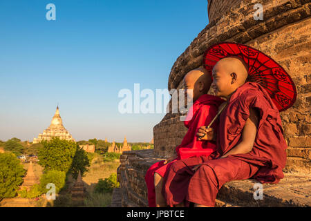 Bagan, Mandalay region, Myanmar (Burma). Two young monks sitting on top of a stupa with the Shwesandaw pagoda in - Stock Photo